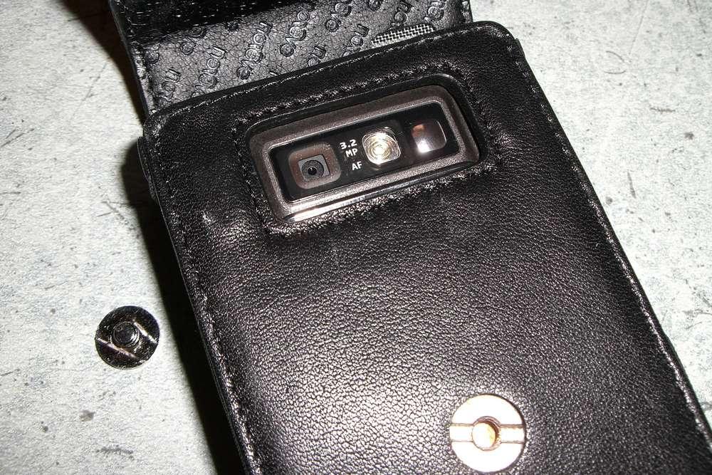 Dos de la housse avec la découpe pour l'appareil photo, les aimants de fermeture (à cauche et à droite de cette découpe) et vis de fixation enlevée.